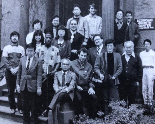A Group of IDE Alumni pose in front of the entrance to the Economic Growth Center